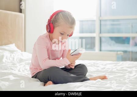 Toute la longueur de l'écoute de la musique sur le casque de fille dans la chambre Banque D'Images