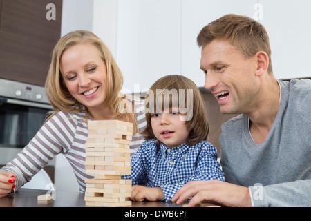 Heureux parents et son fils jouer avec des blocs de bois à la maison Banque D'Images