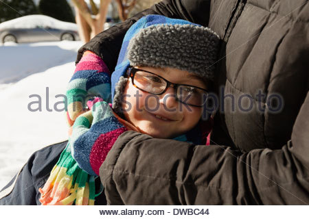 Mother hugging son wearing winter hat and glasses Banque D'Images