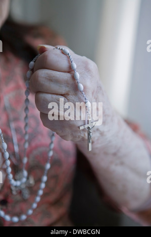 Senior woman holding rosary Banque D'Images
