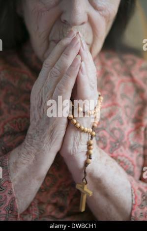 Femme en prière avec le chapelet senior Banque D'Images