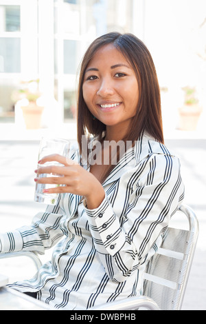Portrait d'une fille asiatique souriante de boire un verre d'eau Banque D'Images
