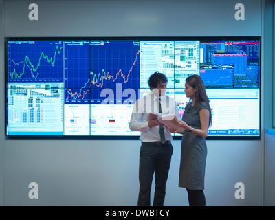 Les gens d'affaires réunion en face d'écrans graphiques Banque D'Images