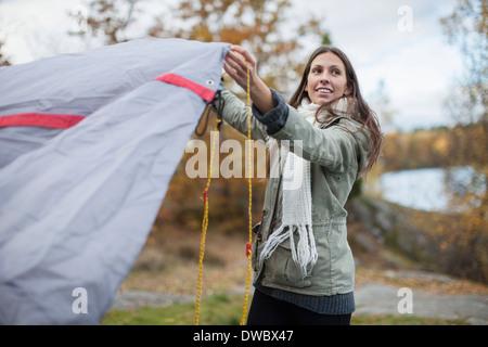 Jeune femme tente mise en place tout en regardant ailleurs dans la forêt Banque D'Images