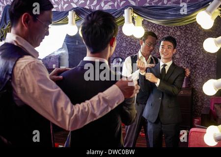 Solutions sur mesure avec les jeunes clients masculins essayant sur nouveau costume traditionnel en boutique Banque D'Images