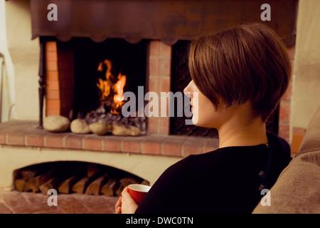 Jeune femme assise sur un canapé avec une tasse de café Banque D'Images