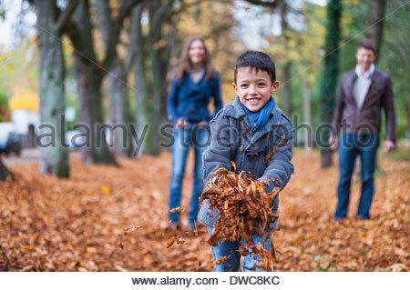 Jeune garçon et les parents la collecte de feuilles d'automne dans le parc Banque D'Images