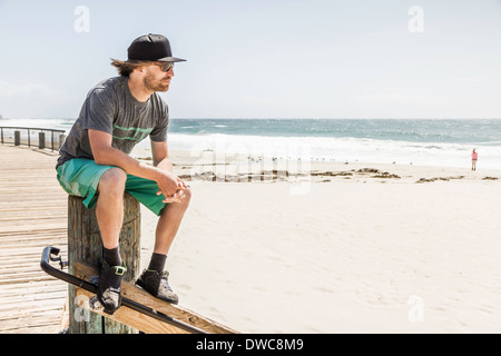 Young man sitting on wooden post, Laguna Beach, Californie, USA Banque D'Images