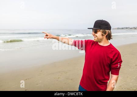 Jeune homme pointant vers la mer, Laguna Beach, Californie, USA Banque D'Images