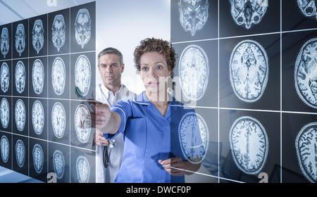 Médecin et infirmière travaillant avec MRI scans du cerveau vu à travers l'affichage interactif Banque D'Images