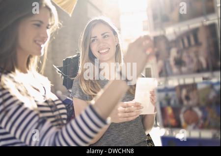 Deux jeunes femmes à la recherche d'amis à cartes postales, Valencia, Espagne Banque D'Images
