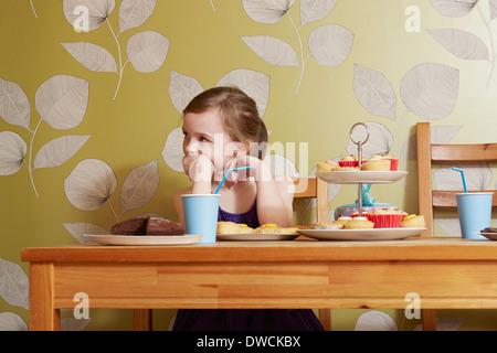S'ennuyer à la fille à table avec cuisine de fête Banque D'Images