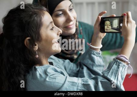 Mère et fille taking self portrait dans la chambre Banque D'Images