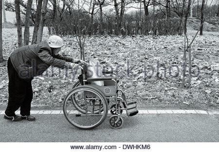 """Une vieille dame avec l'état; 'l'hypercyphose"""" ou """"la bosse de owager', pousse un fauteuil roulant, Chungju, Corée Banque D'Images"""