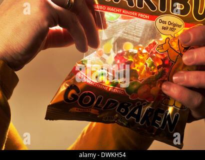 Image symbolique sur le sucre dans les aliments: Woman eating gummy bears.