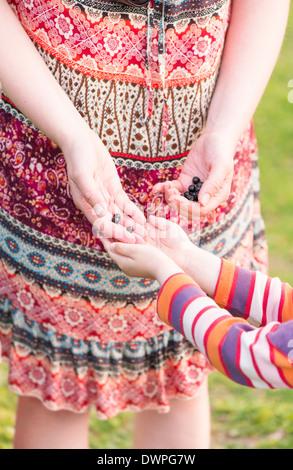 Petite fille aider sa mère choisir noir et de groseille rouge dans le jardin. Banque D'Images