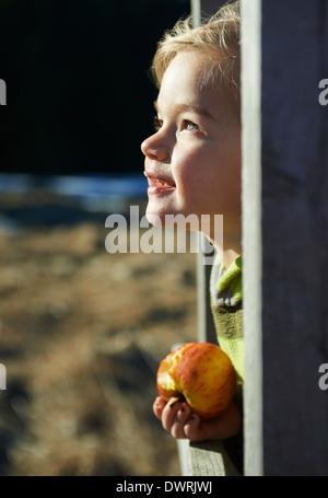 Petite blonde enfant côté fille face portrait eating apple dans la fenêtre en bois au coucher du soleil Banque D'Images