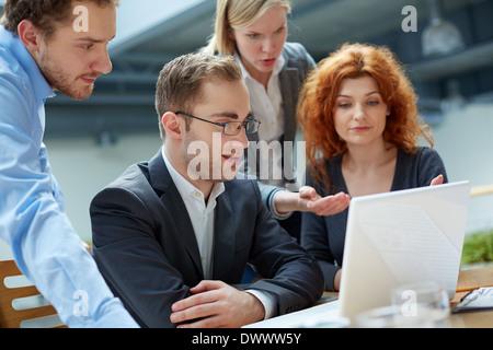Groupe de partenaires d'affaires travaillant avec ordinateur portable à la réunion Banque D'Images