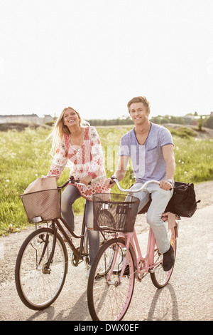 Portrait of young couple cycling on country road Banque D'Images