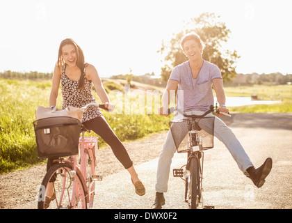 Portrait of happy young couple avec les jambes à vélo sur route de campagne Banque D'Images