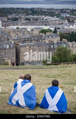 Trois jeunes garçons drapés dans des drapeaux écossais assis sur Calton Hill, à Édimbourg, au cours d'un pro-indépendance Banque D'Images