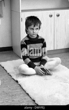 Berlin, Allemagne de l'Est, un petit garçon est assis dans le jardin d'insécurité alimentaire en tailleur sur le Banque D'Images