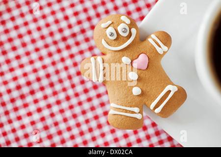 Smiling Gingerbread Man et tasse de café sur la table Banque D'Images