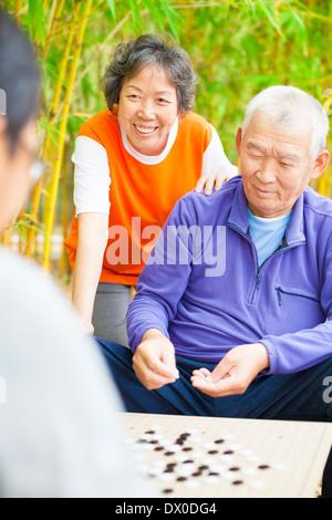Asian seniors jouer avec vos amis weiqi dans le parc Banque D'Images