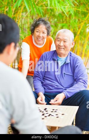 Les personnes âgées de sexe masculin gagner un jeu de société chinois .'weiqi' dans le parc Banque D'Images