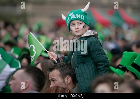 Belfast, Royaume-Uni 16 mars, 2014. Un jeune garçon sur les épaules de son père, d'un drapeau vert avec Shamrock sur elle.