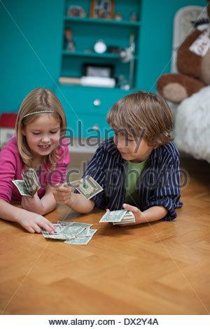 Frère et sœur jouant de l'argent comptant dans la chambre Banque D'Images