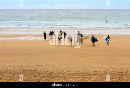 Groupe de surfeurs dans le motion blur walking on beach at sunset Banque D'Images