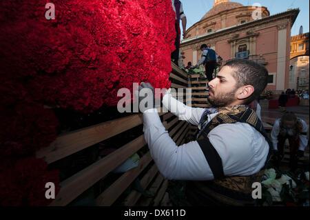 Valence, Espagne. 18 Mar, 2014. Un homme décore la sculpture géante de la Vierge avec des fleurs pendant les Fallas Banque D'Images