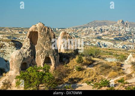Logements en cheminées de fées et d'Uchisar (R) dans la distance, la Vallée Rouge, Cappadoce, Turquie Banque D'Images