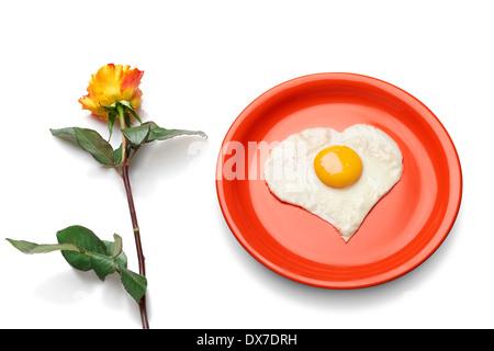 Oeufs en forme de coeur sur la plaque rouge à côté de roses frais. Banque D'Images