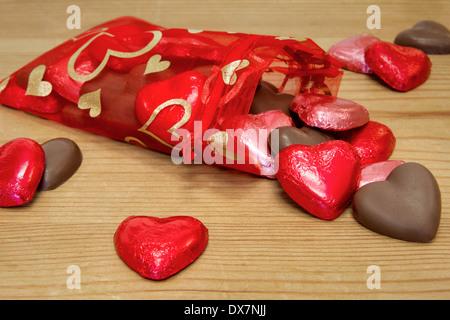 Un sac rouge plein de chocolats en forme de cœur sweetheart tomber sur une table en bois. Banque D'Images