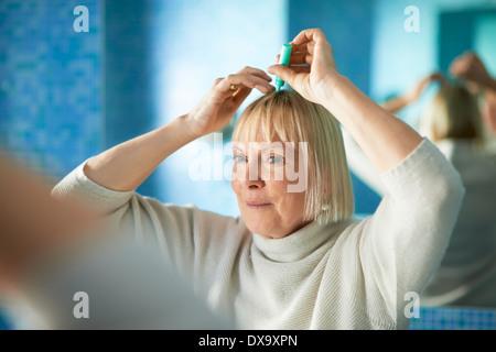 Femme de race blanche de l'application de lotion pour empêcher la perte de cheveux, miroir à maquillage dans la Banque D'Images