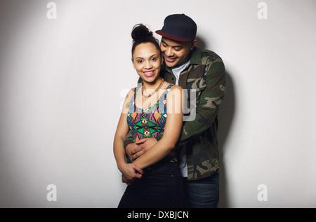 Portrait of happy young man embracing sa belle petite amie par derrière. Jeune couple amoureux sur fond gris Banque D'Images