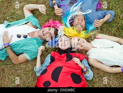 Portrait d'amis en costumes laying in grass at music festival Banque D'Images