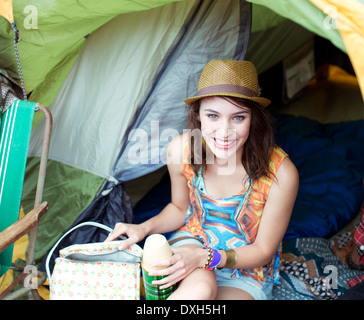 Portrait of smiling woman in tent at music festival Banque D'Images