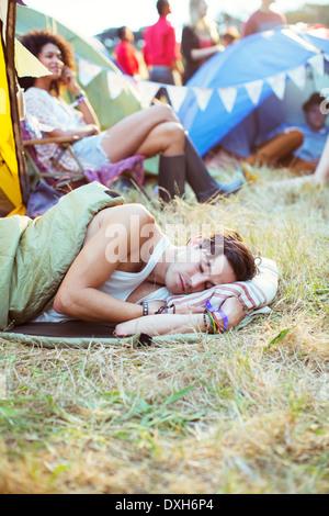 L'homme en sac de couchage tentes dormir dehors au festival de musique Banque D'Images
