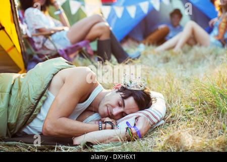 L'homme à tiara dormir dans des tentes à l'extérieur du sac de couchage au festival de musique Banque D'Images