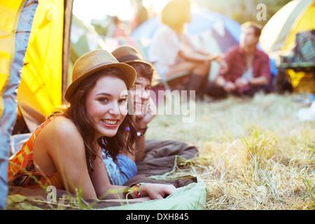 Portrait de couple laying in tent at music festival Banque D'Images
