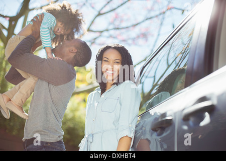 Portrait de femme heureuse avec son mari et sa fille à l'extérieur de voiture Banque D'Images