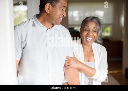 Rire senior couple in doorway Banque D'Images