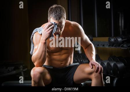 Man fatigué d'essuyer la sueur de front in gym Banque D'Images