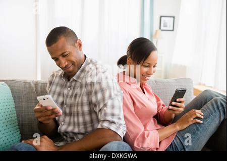 L'utilisation de téléphones cellulaires les deux dos à dos sur le canapé