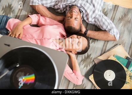 Couple heureux sur un tapis à l'écoute de record player Banque D'Images