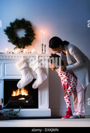 Mère et fille noire à la recherche à des bas de Noël Banque D'Images