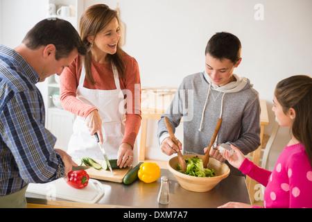 Caucasian family preparing salad in kitchen Banque D'Images